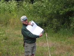 Ron Taskey points out a page in the field guide.